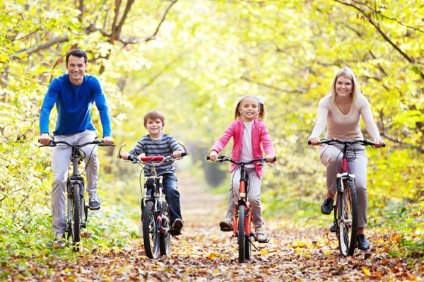 Family of four exercising together on bikes.