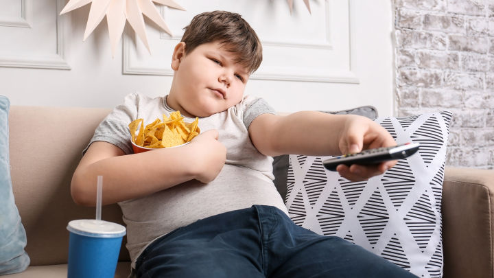 Overweight boy eating chips and sitting on couch.
